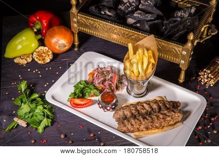 Kebab from chopped mutton, is served with French fries, onions salad and sauce