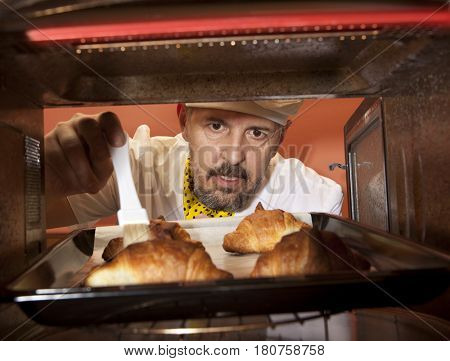 Chef prepares croissant in the oven. View from the inside of the oven. Cooking in the oven