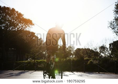 Unrecognizable Male Cyclist Riding Racing Bicycle On Suburban Street. Athletic Young Man Wearing Cyc