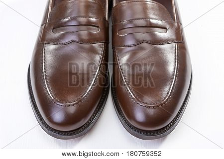 Footwear Concepts. Pair of Stylish Brown Penny Loafer Shoes Against White Background. Placed Together Closely. Horizontal Image Composition