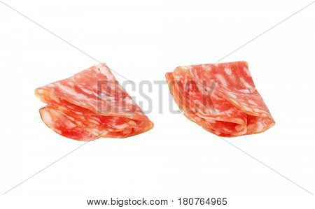 two folded slices of dry salami on white background