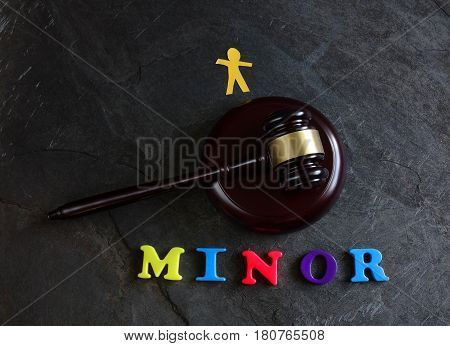 Gavel with Minor spelled out in play letters with paper child figure