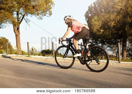 Beautiful Athletic Girl Riding Racing Bike Uphill On Road Against Nature Background. Young European