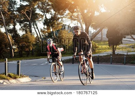 Happy Athletic Couple Enjoying Morning Ride On Racing Bicycles, Speeding On Desert Street. Young Eur