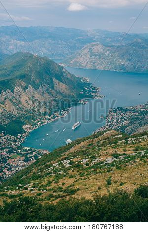 Bay of Kotor from the heights. View from Mount Lovcen to the bay. View down from the observation platform on the mountain Lovcen. Mountains and bay in Montenegro. The liner near the old town of Kotor.