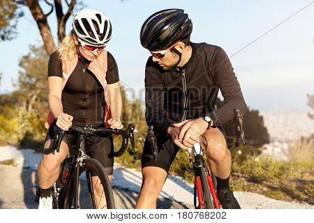 Active Healthy Urban Lifestyle. Young Couple Relaxing While Cycling In City Park: Beautiful Blonde W