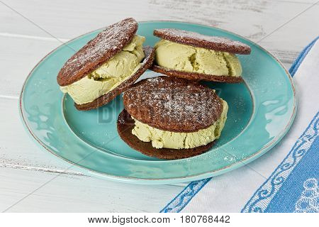 Three homemade matcha tea ice cream sandwiches on a turquoise plate against a white painted background.