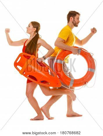 Lifeguards running with rescue tube and ring buoy on duty. Man and woman supervising swimming pool. Accident prevention.