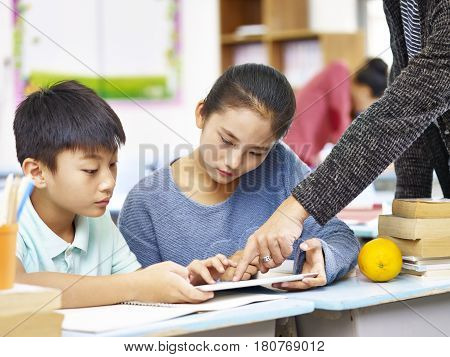 two asian elementary school children using digital tablet with help from teacher tutor in classroom.