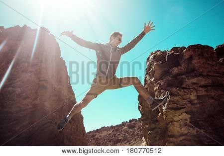 Man running fast to jump over precipice between two mountains.