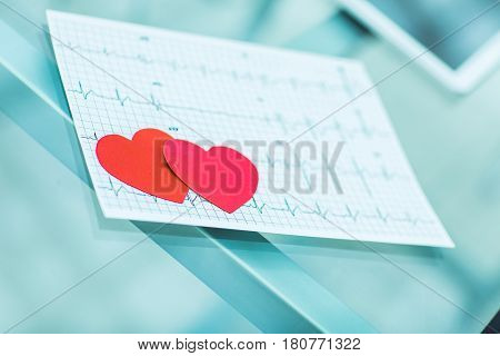 two red paper heart on the electrocardiogram, the cardiologist.the photo is a blank space for your text