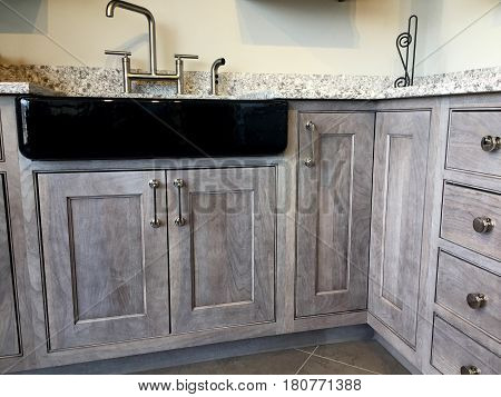 Gray kitchen cabinets. Contemporary base cabinets with granite kitchen countertop. Wood Cabinets. Contemporary Italian kitchen cabinet design. Stainless steel farm sink and faucet with wooden kitchen cabinet.
