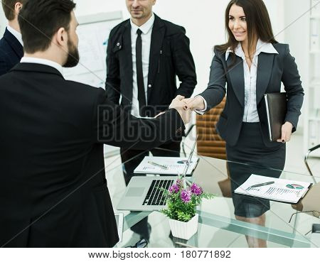 handshake business partners at the meeting near the desktop in a modern office.the photo has a empty space for your text