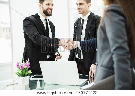 members of the business team and the handshake of the Manager and the client prior to conclusion of contract in a modern office.