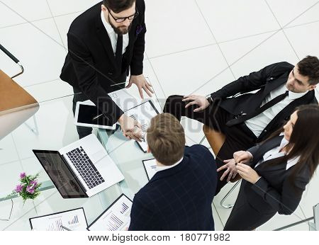 top view - handshake of business partners before the presentation of a new project in a modern office