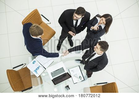 top view - reliable handshake business partners after the discussion of the financial contract in the office.the photo has a empty space for your text.