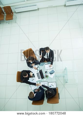 top view - handshake of business partners at a business meeting at the workplace in the spacious office. the photo is a blank space for your text