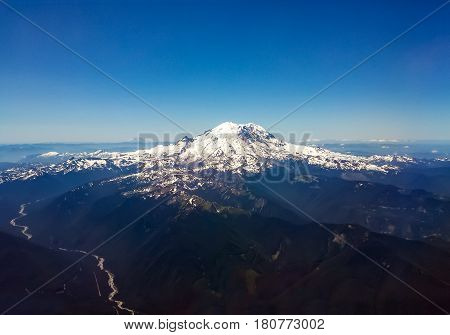 Aerial view of big snow capped volcanic mountain peak in a Pacific Northwest landscape scene