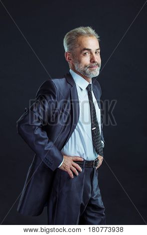 confident businessman in a business suit on a black background.the photo has a empty space for your text