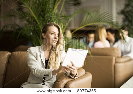 Successful business woman with a digital tablet sitting on the couch in the lobby of a modern office