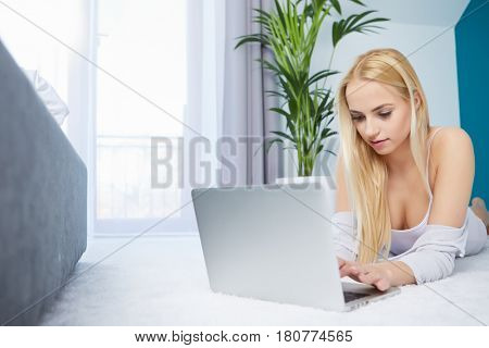 Smiling woman lying on rug using her laptop at home in the living room