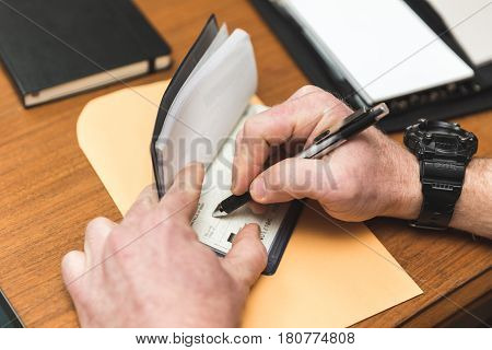 Man writing a check in a checkbook. Envelope and notepads are nearby. Man is wearing watch on right-hand wrist.