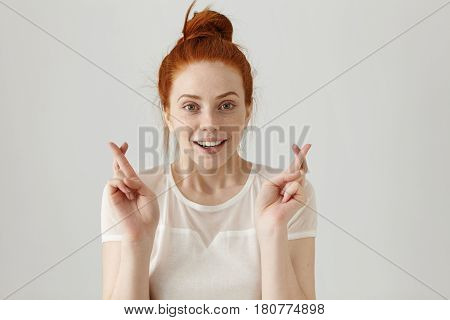 Body Language. Superstitious Teenager Girl With Ginger Hair And Pretty Face Crossing Fingers For Goo