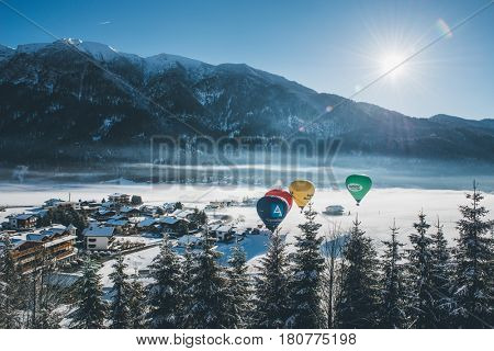 ACHENKIRCH (AUSTRIA) - CIRCA MARCH 2017: Four hot air balloons flying over an alpine resort nestling in a snowy valley below rugged mountain peaks