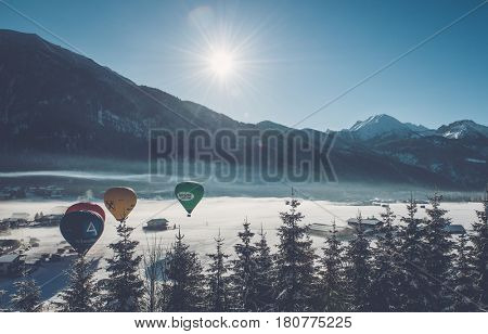 ACHENKIRCH (AUSTRIA) - CIRCA MARCH 2017: Four hot air balloons flying over a ski resort nestling in a snowy valley alongside a frozen lake on a cold sunny winter day