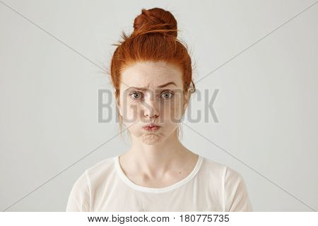 Annoyed Irritated Young Red-haired Female With Freckles Blowing Her Cheeks, Frowning, Feeling Frustr