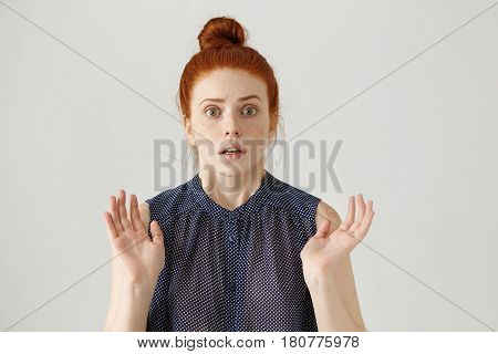 Studio Portrait Of Stunned Or Frightened Young Lady With Ginger Hair Gesturing With Both Hands, Havi