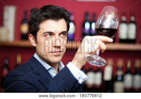 Man tasting red wine in a tavern