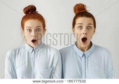Human Emotions. Two Beautiful Ginger Girls Wearing Identical Blue Shirts And Hairstyles Looking In A