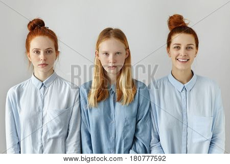 Beauty youth people and lifestyle. Three attractive female friends dressed in similar blue shirts posing at studio. Serious freckled blonde teenage girl standing between her two red-haired sisters