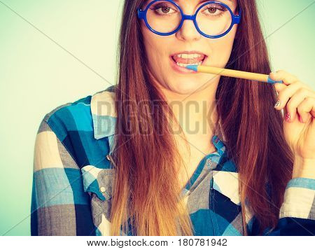 Studying education and fun concept. Nerdy woman in weird big glasses. Studio shot on blue background