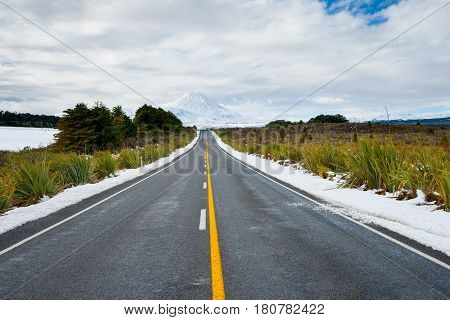 Long yellow center line along road through winter landscape leading to Mount Ngauruhoe in North Island New Zealand.