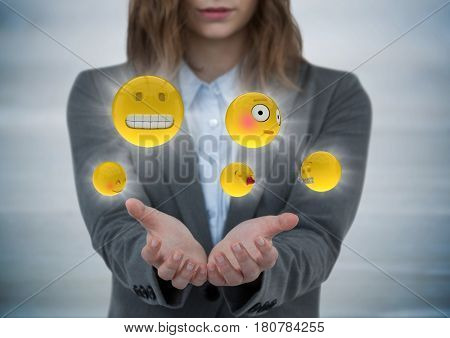 Digital composite of Business woman with hands out and emojis with flares against grey wood panel
