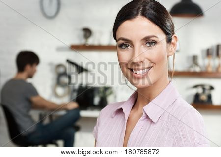 Closeup portrait of attractive young woman smiling happy, looking at camera.