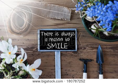 Sign With English Quote There Is Always A Reason To Smile. Sunny Spring Flowers Like Grape Hyacinth And Crocus. Gardening Tools Like Rake And Shovel. Hemp Fabric Ribbon. Aged Wooden Background