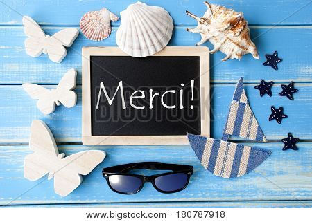 Flat Lay Of Chalkboard On Blue Wooden Background. Nautical Summer Decoration As Holiday Greeting Card. French Text Merci Means Thank You