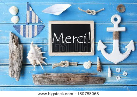 Flat Lay Of Chalkboard On Blue Wooden Background. Nautic Or Maritime Summer Decoration As Holiday Greeting Card. French Text Merci Means Thank You