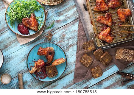 Top view dinner table with chicken wings in cranberry sauce. Rustic style. Homemade dinner party concept