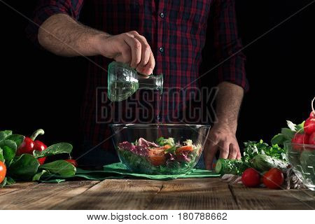 Man pours olive oil in a bowl of salad. Cooking tasty and healthy meal