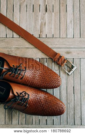Brown man's shoes with laces on a wooden background and a brown belt.