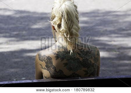 Montreal, Quebec - July 27, 2016 -- Close up of the upper back of a blond woman with a beautiful tattoo on her back on a sunny day in a park in Montreal, Quebec in late July.