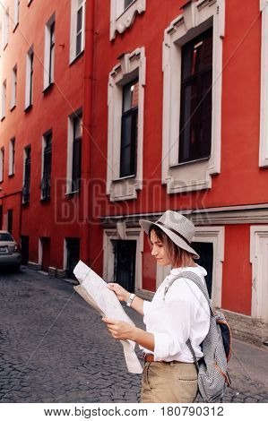 Travel guide. Young female traveler with backpack and with map on the street. Travel concept. Adventure