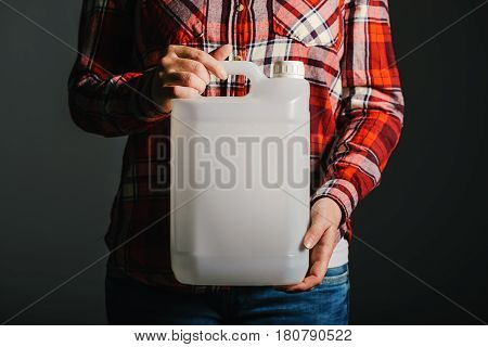 Unrecognizable female farmer with unlabeled plastic tank canister containing pesticides for plant processing in agriculture