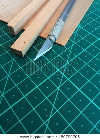 Close up of hobby knife and balsa wood on cutting mat