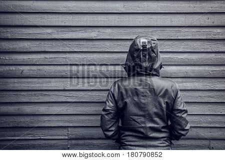 Unrecognizable hooded female person facing wooden wall monochromatic black and white image