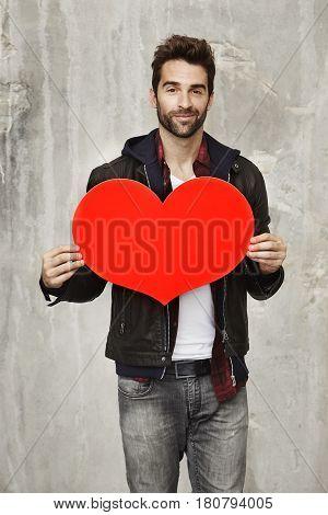 Dude in love holding valentine heart portrait studio